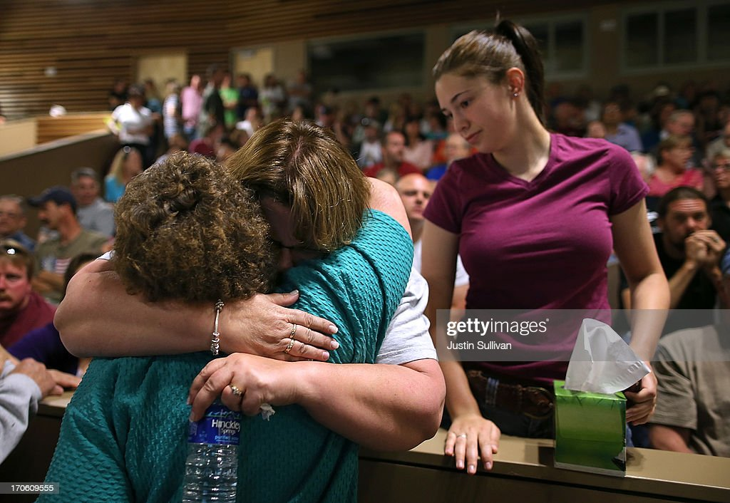 Residents embrace before the start of a community meeting to update the status of the fire at Palmer Ridge High School on June 15, 2013 in Monument, Colorado. The Black Forest fire is the most destructive in Colorado history, having consumed more than 15,000 acres as of this morning while destroying 473 homes. Two people have died in the fire.