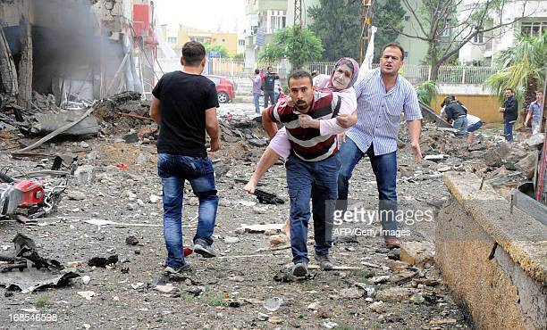 Residents evacuate a wounded woman to hospital after car bombs exploded on May 11 2013 near the town hall in Reyhanli just a few kilometres from the...