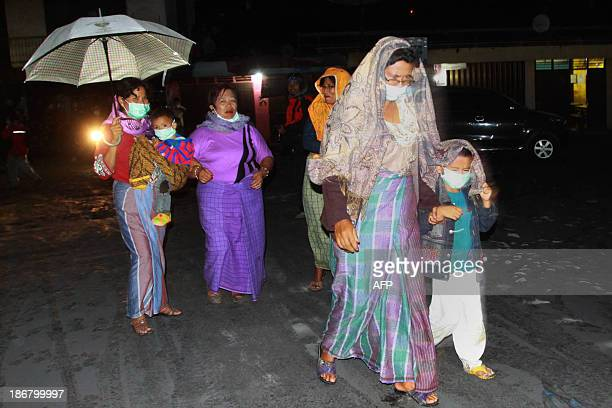 Residents evacuate to temporary shelters in Karo district in Sumatra island on November 4 2013 as Mount Sinabung volcano in western Indonesia erupted...