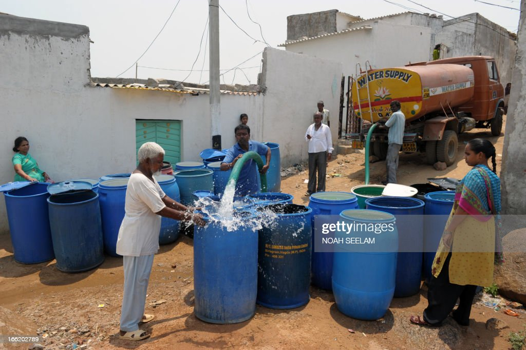 Residents fill containers with potable drinking water from a government water supply tanker at a slum in Hyderabad on April 10, 2013. Water shortages are a problem in the southern Indian city as summer temperatures soar above 40 degrees Celsius. AFP PHOTO / Noah SEELAM