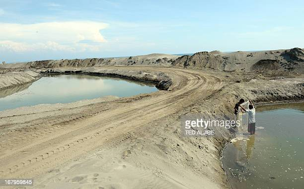 Residents fish on a makeshift pond after magnetite or black sand were quarried along the shoreline in Caparadacan Caoayan town Ilocos sur province...