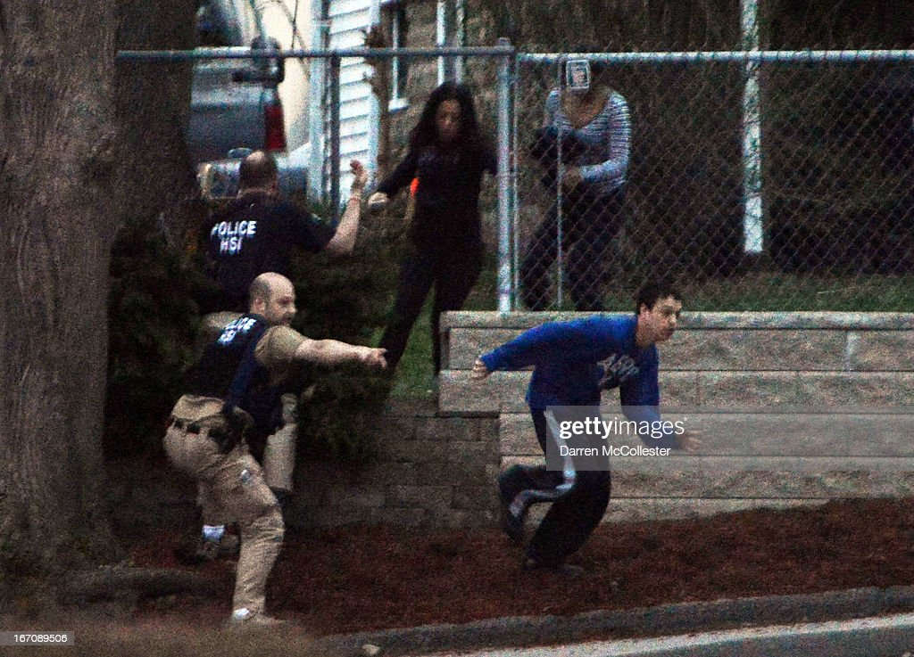 Residents flee from an area where a suspect is hiding on Franklin St., on April 19, 2013 in Watertown, Massachusetts. After a car chase and shoot out with police, one suspect in the Boston Marathon bombing, Tamerlan Tsarnaev, 26, was shot and killed by police early morning April 19, and a manhunt is underway for his brother and second suspect, 19-year-old Dzhokhar A. Tsarnaev. The two men are suspects in the bombings at the Boston Marathon on April 15, that killed three people and wounded at least 170.