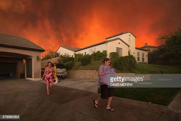 TOPSHOT Residents flee their home as flames from the Sand Fire close in on July 23 2016 near Santa Clarita California Fueled by temperatures reaching...