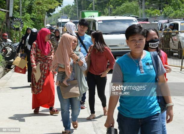 Residents fleeing from Marawi walk through a checkpoint at the entrance of Iligan on southern Philippine island of Mindanao on May 24 2017 Philippine...