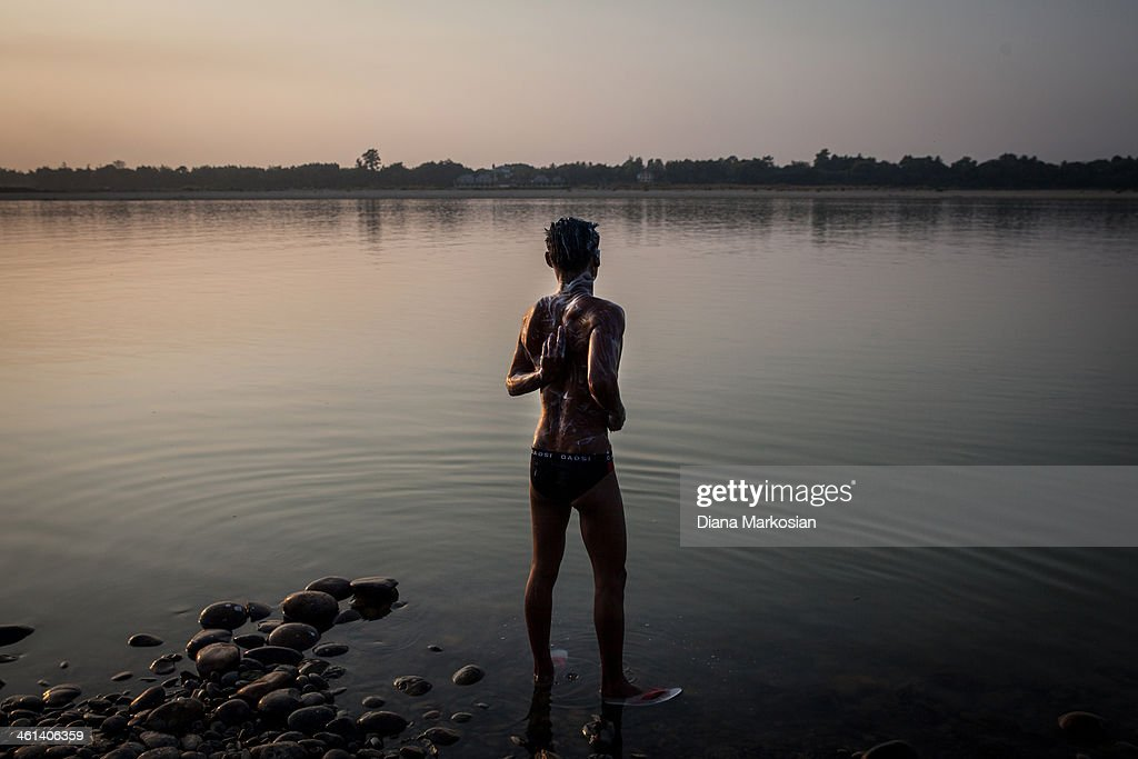 Residents from Kachin state bathe in the Irrawaddy River at sunset on December 27, 2013 in Kachin State, Myanmar. The Irrawaddy River is the lifeline of Burma, running through the center of the country. The River provides vital nutrients to wetlands and floodplain areas downstream, including the delta region which provides nearly 60 percent of Burma's rice. A massive Chinese hydropower project is under construction in the Irrawaddy river, despite fierce opposition from the Kachin Independence Organization, which broke a 17-year-ceasefire after warning that it would fight to block the project. In 2011, the hydroelectric dam project was suspended under the mandate of President U Thein Sein. The project, which involves building a 152-meter-tall hydroelectric dam at the confluence of the two rivers that form the Irrawaddy, is the brainchild of a giant Chinese state-owned firm, China Power International.