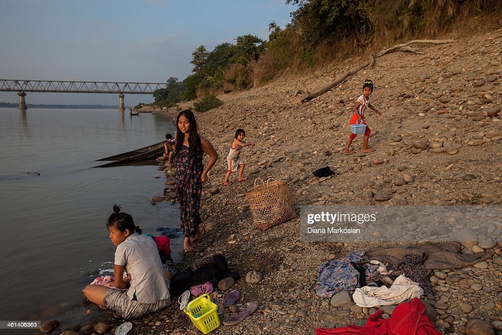 Residents from Kachin state bathe in the Irrawaddy River at sunset on December 28, 2013 in Kachin State, Myanmar. The Irrawaddy River is the lifeline of Burma, running through the center of the country. The River provides vital nutrients to wetlands and floodplain areas downstream, including the delta region which provides nearly 60 percent of Burma's rice. A massive Chinese hydropower project is under construction in the Irrawaddy river, despite fierce opposition from the Kachin Independence Organization, which broke a 17-year-ceasefire after warning that it would fight to block the project. In 2011, the hydroelectric dam project was suspended under the mandate of President U Thein Sein. The project, which involves building a 152-meter-tall hydroelectric dam at the confluence of the two rivers that form the Irrawaddy, is the brainchild of a giant Chinese state-owned firm, China Power International.