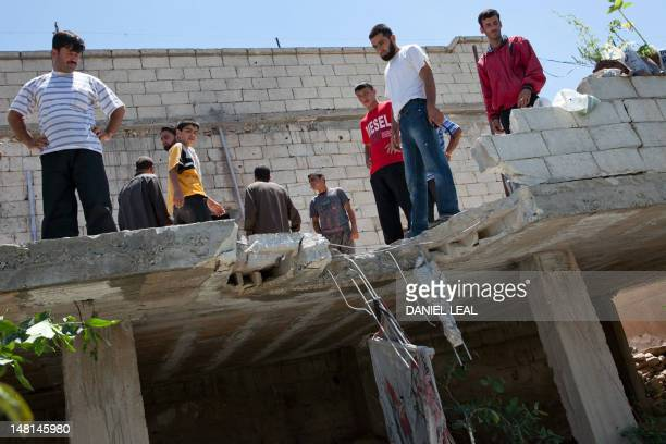 Residents from Kfar Sajna look at the roof of a house on July 10 allegedly damaged after a tank shell was fired by Syrian government forces based in...