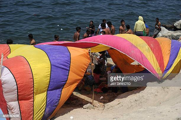 Residents from slum areas escape the summer heat by relaxing in the waters of Manila Bay on April 4 despite warnings issued by city and national...