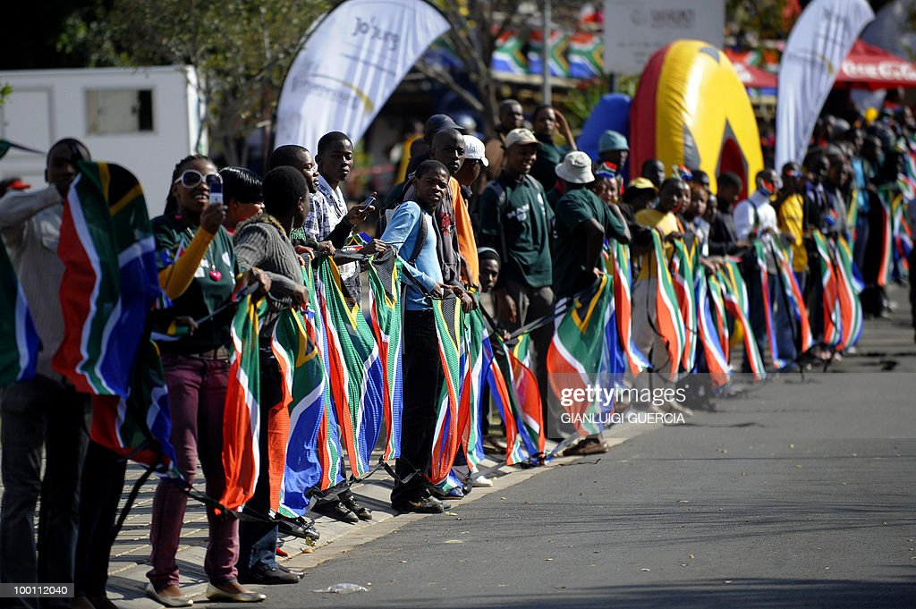 Residents from Soweto hold South African flags as they wait for a parade to pass on May 21, 2010 during the official celebration marking 20 days ahead of the FIFA WC2010 kick off, in Johannesburg, South Africa. South Africa will host the FIFA World Cup football event from the 11 of June to the 11 of July, 2010.