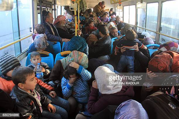 TOPSHOT Residents from the mostly Shiite Syrian villages of Kafraya and Fuaa which are besieged by opposition fighters wait in a bus to get a green...