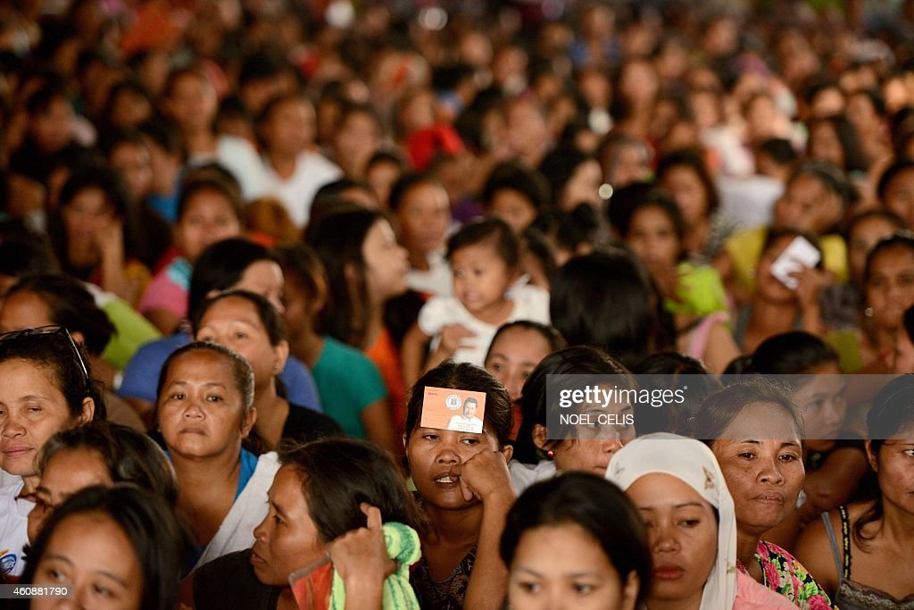 Residents from the slum area of Baseco, Tondo in Manila wait at the start of a gift giving program by former Philippine President and Manila Mayor <a gi-track='captionPersonalityLinkClicked' href=/galleries/search?phrase=Joseph+Estrada&family=editorial&specificpeople=553277 ng-click='$event.stopPropagation()'>Joseph Estrada</a> on December 29, 2014. The gift giving program is held inside a covered court in Manila with former President Estrada handing out gifts to the residents of Baseco. AFP PHOTO / NOEL CELIS