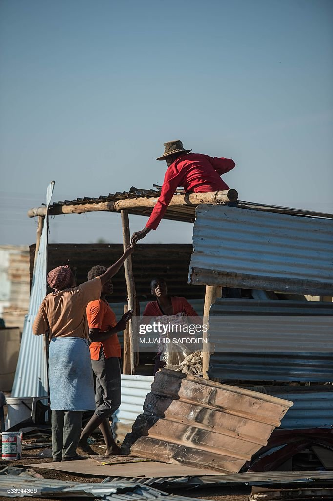 Residents from the township of Hammanskraal rebuild their shacks after a forced eviction took place causing violent unrest on May 24, 2016 in Hammanskraal, North of Pretoria. Two people related to the eviction company were reportedly killed on May 23. / AFP / MUJAHID