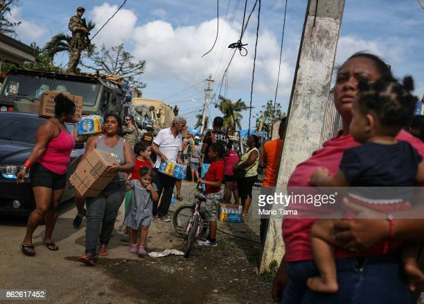 Residents gather and receive food and water provided by FEMA in a neighborhood without grid electricity or running water on October 17 2017 in San...