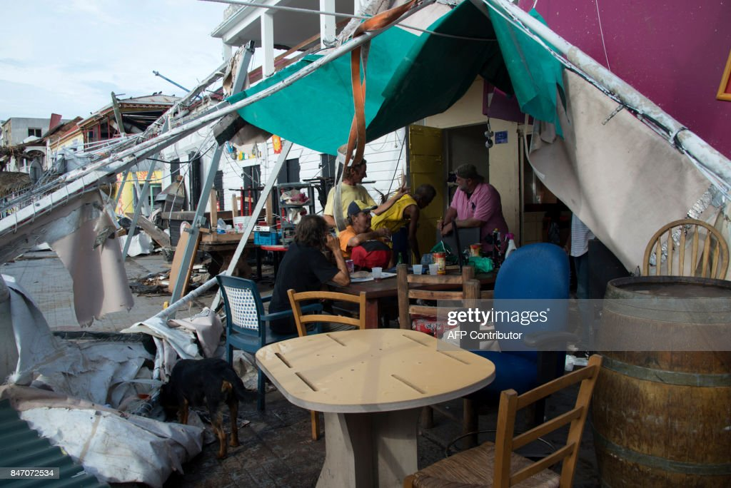 TOPSHOT - Residents gather at a bar, that is damaged, on September 14, 2017 in Marigot on the French Caribbean island of Saint Martin, after the island was hit by Hurricane Irma. The Category 4 hurricane, which struck in 1995, killed 19 people in St Martin, Antigua, Barbuda, St Barts and Anguilla and left tens of thousands homeless. Irma left 15 dead on both sides of St Martin. PHOTO / Helene Valenzuela