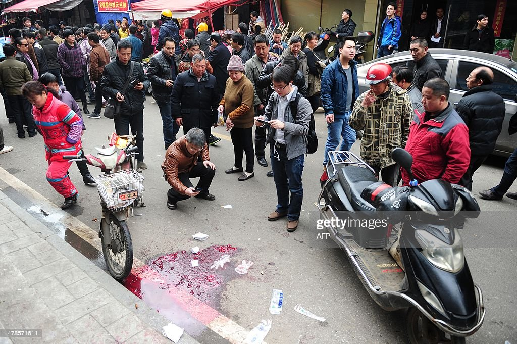 Residents gather at the scene where attackers armed with knives killed three people in Changsha, central China's Hunan province on March 14, 2014. Attackers armed with knives killed three people in China on March 14, an official said, ruling out terrorism two weeks after a mass stabbing blamed on Xinjiang militants left 29 people dead and stunned the nation. CHINA