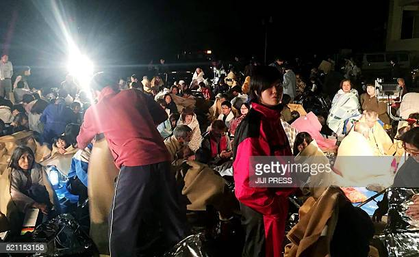 TOPSHOT Residents gather for shelter in front of the town hall following an earthquake at Mashiki town in Kumamoto prefectuire on April 14 2016 The...