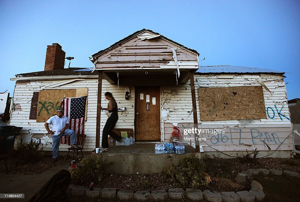 Residents gather in front of their damaged home after a massive tornado passed through the town killing at least 126 people on May 26, 2011 in Joplin, Missouri. The town continues the process of recovering from the storm which damaged or destroyed an estimated 8,000 structures.
