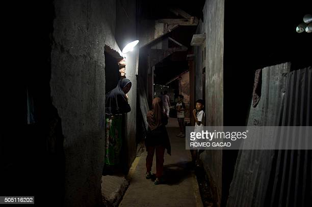 Residents gather in the neighborhood of suspected terrorist Muhammad Ali on January 15 2016 in Jakarta who died in the January 14 2016 bomb attacks...