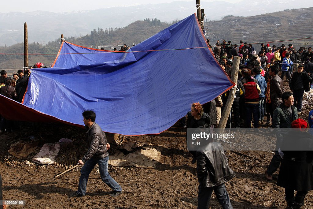 Residents gather near a temporary tent to identiy remains of the dead after the rescue mission is finished in the disaster-hit area in Gaopo village, southwest China's Yunnan province on January 12, 2013. Three people remain missing after a landslide which killed 43, including seven from a single family, struck a remote village in southwestern China, state media said on January 12. CHINA
