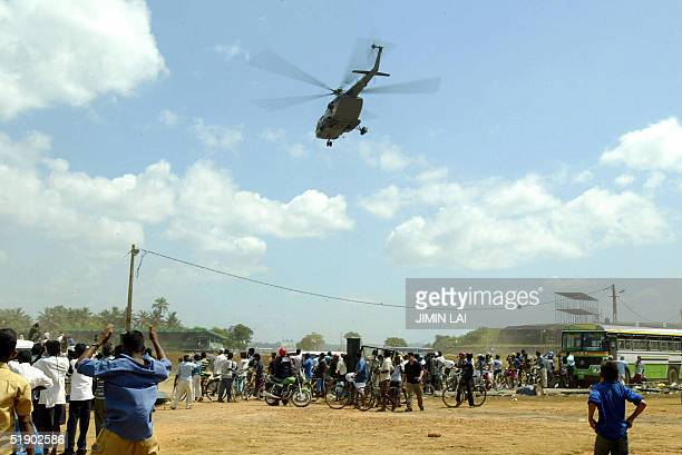Residents gather near an Indian airforce helicopter carrying an injured westerner in the southwestern Sri Lankan coastal town of Galle 30 December...