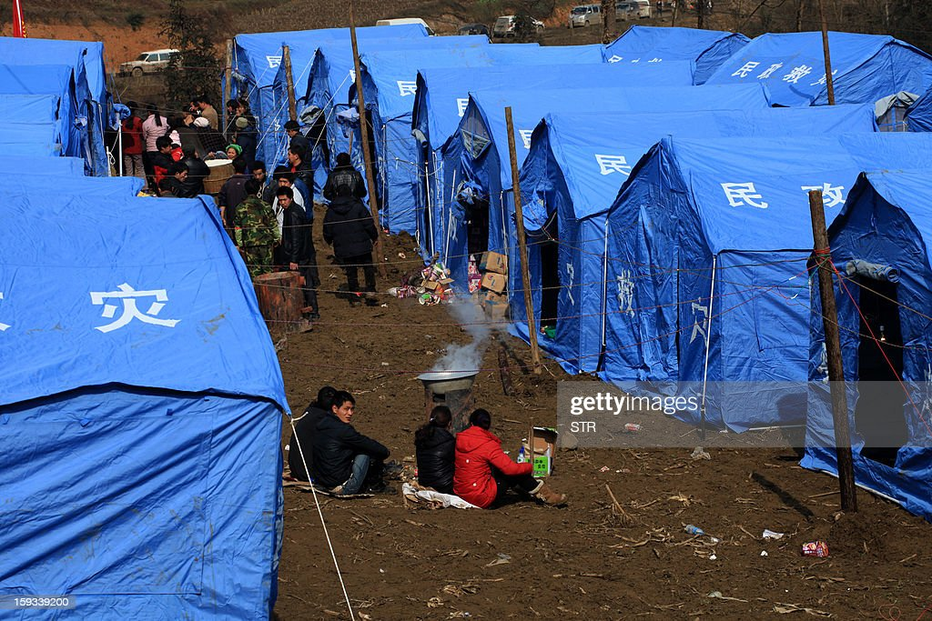 Residents gather near temporary tents after the rescue mission is finished in the disaster-hit area in Gaopo village, southwest China's Yunnan province on January 12, 2013. Three people remain missing after a landslide which killed 43, including seven from a single family, struck a remote village in southwestern China, state media said on January 12. CHINA