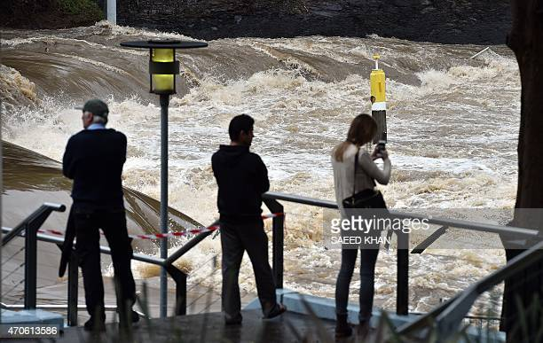 Residents gather to look at the overflowing Parramatta river at the flooded Parramatta ferry wharf in Sydney on April 22 2015 A stormtossed ship...