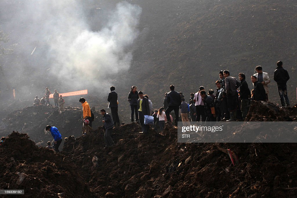 Residents gather to mourn the dead after the rescue mission is finished in the disaster-hit area in Gaopo village, southwest China's Yunnan province on January 12, 2013. Three people remain missing after a landslide which killed 43, including seven from a single family, struck a remote village in southwestern China, state media said on January 12. CHINA