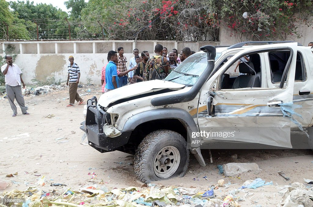 Residents gather to see a car damaged by a roadside bomb explosion near a street in Mogadishu on January 12, 2013. According to witnesses one soldier was injured in the explosion which was targeting the pickup truck belong to a Somali lawmaker. AFP Photo/Mustafa Abdi
