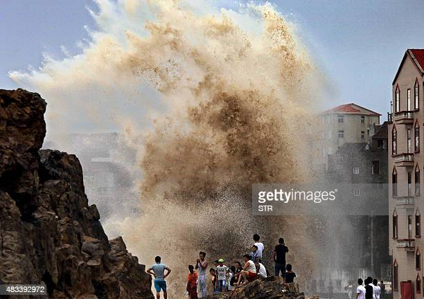 Residents gather to see huge waves stirred up by strong wind as typhoon Soudelor draws near the mainland of China in Wenling east China's Zhejiang...