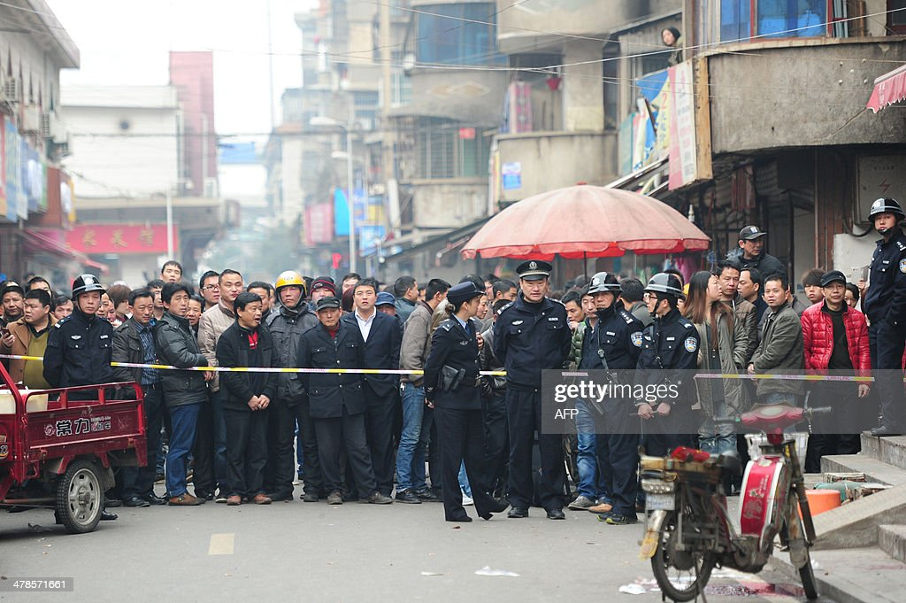 Residents gather to watch as police stand guard at the scene where attackers armed with knives killed three people in Changsha, central China's Hunan province on March 14, 2014. Attackers armed with knives killed three people in China on March 14, an official said, ruling out terrorism two weeks after a mass stabbing blamed on Xinjiang militants left 29 people dead and stunned the nation. CHINA