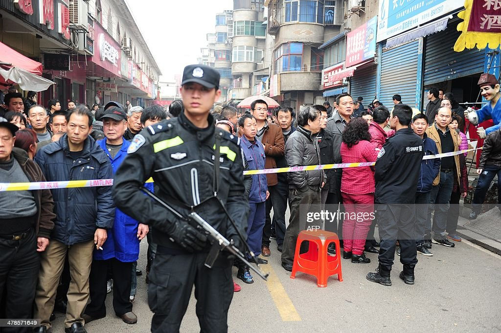 Residents gather to watch as SWAT police stand guard at the scene where attackers armed with knives killed three people in Changsha, central China's Hunan province on March 14, 2014. Attackers armed with knives killed three people in China on March 14, an official said, ruling out terrorism two weeks after a mass stabbing blamed on Xinjiang militants left 29 people dead and stunned the nation. CHINA