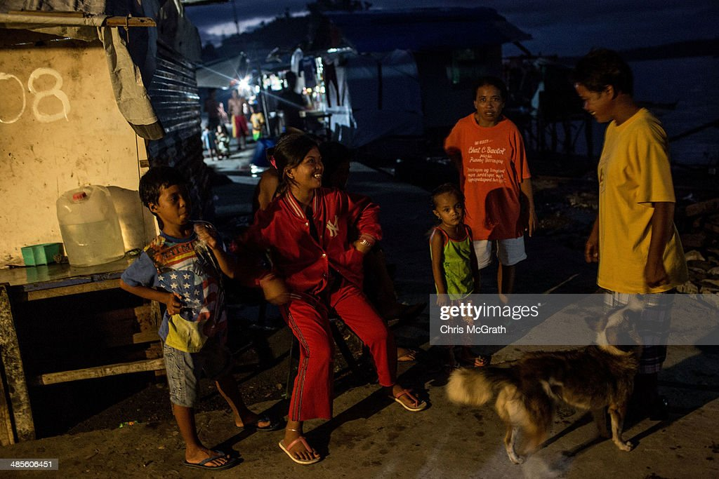Residents gather under a light in the coastal area renamed by residents ' Yolanda Village' on April 19, 2014 in Tacloban, Leyte, Philippines. People continue to rebuild their lives five months after Typhoon Haiyan struck the coast on November 8, 2013, leaving more than 6000 dead and many more homeless. Although many businesses and services are functioning, electricity and housing continue to be the main issues, with many residents still living in temporary housing conditions due to 'No Build' areas preventing them from rebuilding their homes. This week marks Holy Week across the Philippines and will see many people attending religious activities.