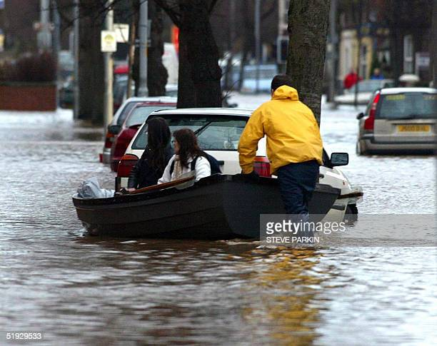 Residents get a boat ride home from rescue workers in Carlisle 09 January 2005 At least 14 people died more than 1000 homes were flooded and hundreds...