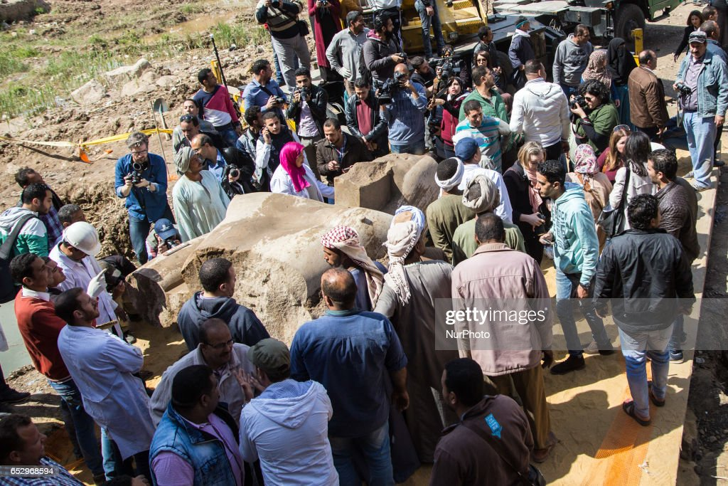 Residents greet antiquities officials after a crane lifts parts of a massive statue, that may be of pharaoh Ramses II, one of the country's most famous ancient rulers, out of groundwater in a Cairo slum, Egypt, Monday, March 13, 2017.