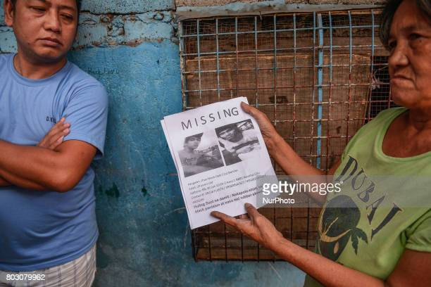 Residents hand out posters calling for the whereabouts of John Bondoc who went missing in Navotas north of Manila Philippines March 28 2017...