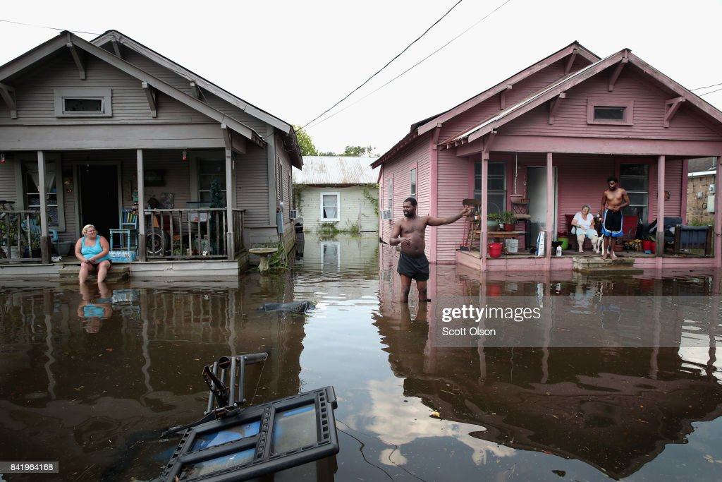 Residents hang out in front of their homes which are surrounded by floodwater after torrential rains pounded Southeast Texas following Hurricane and Tropical Storm Harvey causing widespread flooding on September 2, 2017 in Orange, Texas. Harvey, which made landfall north of Corpus Christi August 25, has dumped nearly 50 inches of rain in and around areas Houston.