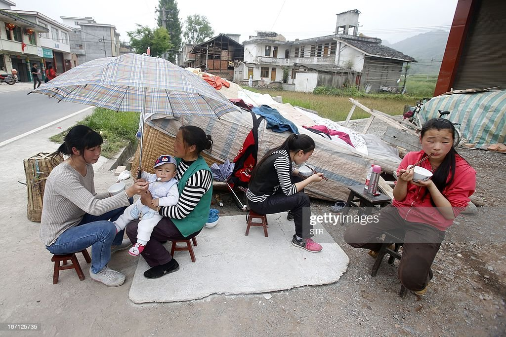Residents have their meals by the roadside after the earthquake in Longmen township in Ya'an, southwest China's Sichuan province on April 21, 2013. Thousands of rescue workers combed through flattened villages in southwest China on April 21 in a race to find survivors from a powerful quake as the toll of dead and missing rose past 200. CHINA