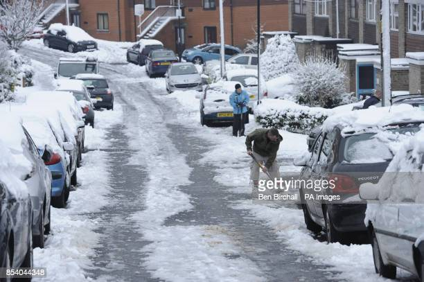 Residents help to clear snow and ice from a residential culdesac at the top of a steep hill in Brislington Bristol