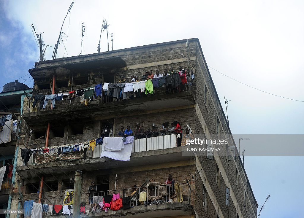 Residents in neighbouring building watch from their balconies as rescuers search for bodies trapped in rubble on May 2, 2016 at the scene of a collapsed residential building in the low-income suburb of Huruma in Nairobi. The death toll in the collapse of a six-storey building in Nairobi on April 29 rose to 21 on May 2 after four more bodies were pulled from the rubble of the residential structure that gave way during weekend storms. / AFP / TONY