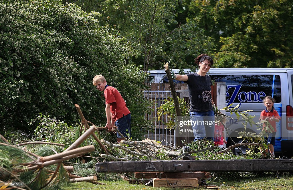 Residents in the Auckland suburb of Whenuapai work to clear storm debri following a tornado that struck yesterday on December 7, 2012 in Auckland, New Zealand. Police today named the three men killed whilst working on a construction site when the tornado hit.