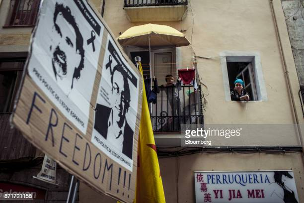 Residents in the Raval neighbourhood watch from their homes as protesters march with photographs of Catalan activists Jordi Sanchez...