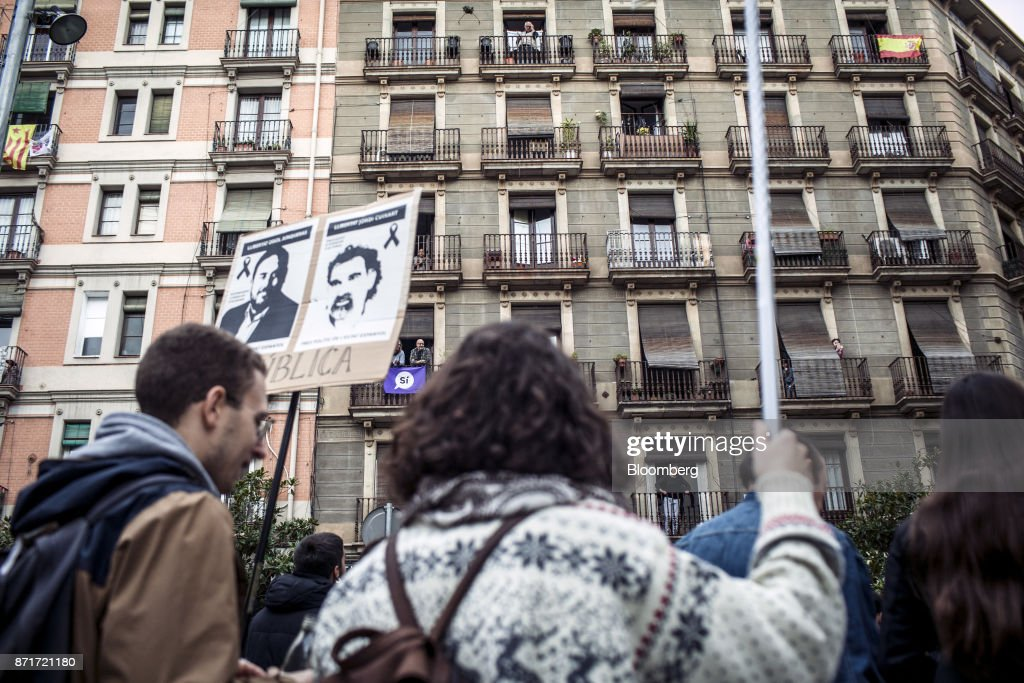 Residents in the Raval neighbourhood watch from their homes as protesters march with photographs of Catalan activistsJordi Sanchez andJordiCuixartand call for 'Freedom for political prisoners' during a regional strike called by pro-independence union in Barcelona, Spain, on Wednesday, Nov. 8, 2017. Spanish Prime MinisterMariano Rajoyinvoked extraordinary powers last month to reassert his authority over Catalonia and fire Catalan presidentCarles Puigdemont and his government.Photographer: Angel Garcia/Bloomberg via Getty Images