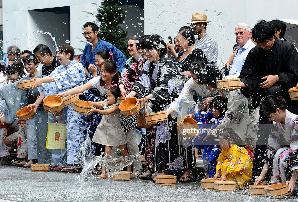 Residents in 'yukata,' or summer kimonos, throw water to the ground at the Ginza shopping district in Tokyo on August 4, 2013. Hundreds of Yukata-clad people participated in the annual summer event to cool off amid high summer temperatures.