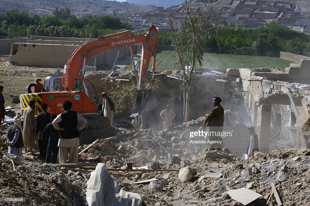 Residents inspect the damage as a bulldozer works at the scene after a weapon's stockpile exploded at a checkpoint in Kandahar Afghanistan on April...