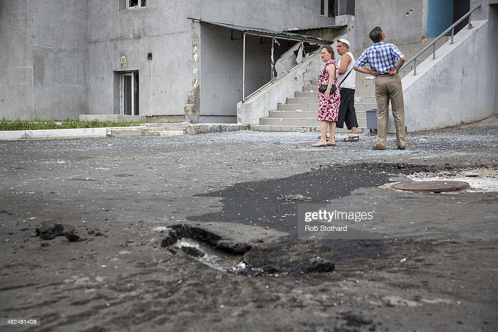 Residents inspect their apartment building, badly damaged by shrapnel from a rocket that landed in front of the building on July 21, 2014 in Donetsk, Ukraine. Local authorities warned residents in the area not to go outside or leave their homes whilst intense shelling set a market ablaze close to the station. The security situation is continuing to affect the investigation into the Malaysian Airlines flight MH17 crash and it is still unclear where or when the train containing the bodies of victims will be moved. Malaysian Airlines flight MH17 was travelling from Amsterdam to Kuala Lumpur when it crashed killing all 298 on board including 80 children. The aircraft was allegedly shot down by a missile and investigations continue over the perpetrators of the attack.