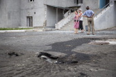 Residents inspect their apartment building badly damaged by shrapnel from a rocket that landed in front of the building on July 21 2014 in Donetsk...