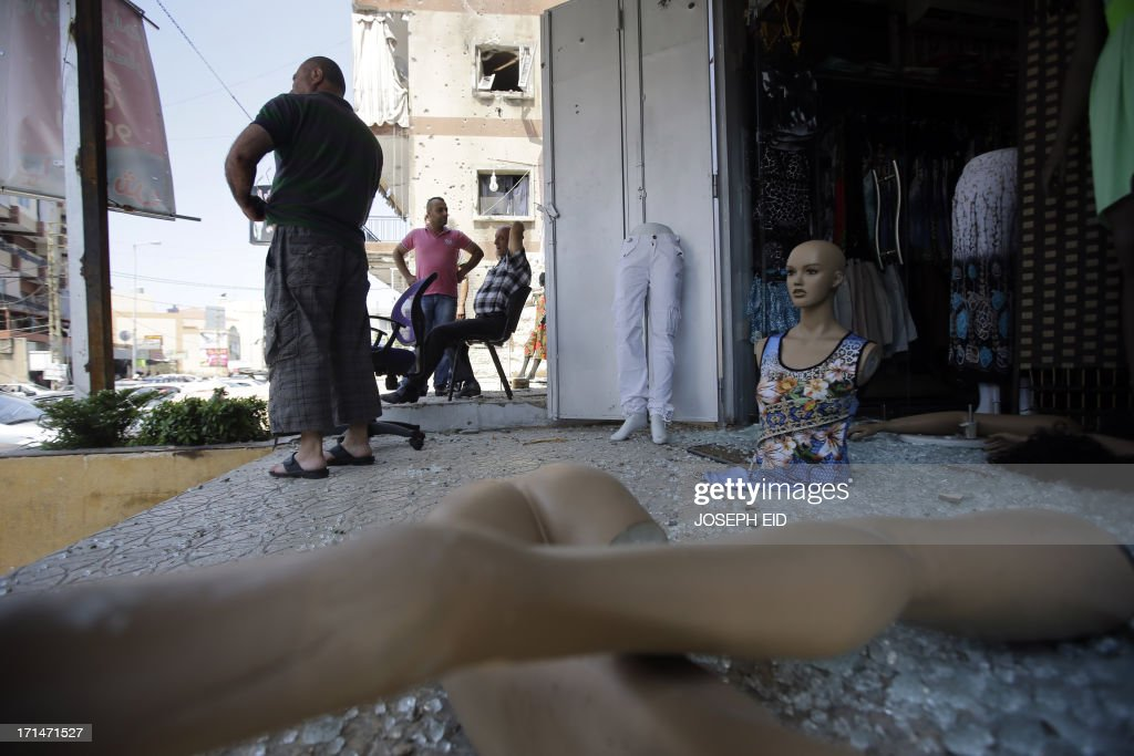 Residents inspect their damaged shops near the Bilal bin Rabah mosque in the Abra district of the southern city of Sidon on June 25, 2013, after troops seized control of the headquarters of a radical Sunni sheikh whose supporters battled the army for two days, killing 16 soldiers.