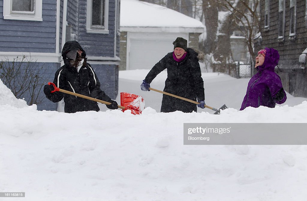 Residents Kristin Irvin, from left, Sarah Chapple-Sokol and Mary Patterson laugh while digging out their driveway after Winter Storm Nemo in Somerville, Massachusetts, U.S., on Saturday, Feb. 9, 2013. More than two feet of snow fell on parts of the U.S. Northeast as high winds left hundreds of thousands of people in the region without power, closed highways and forced the cancellation of 4,700 flights. Photographer: Kelvin Ma/Bloomberg via Getty Images