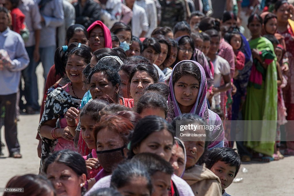 Residents line up for food in an evacuation area set up by the authorities in Tundhikel park on April 27 2015 in Kathmandu Nepal A major 78...