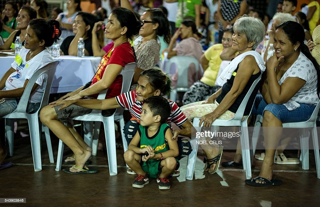 Residents listen as Philippine President Rodrigo Duterte gives a speech as he visited families living in slum area in Manila on June 30, 2016. Authoritarian firebrand Rodrigo Duterte was sworn in as the Philippines' president on June 30, after promising a ruthless and deeply controversial war on crime would be the main focus of his six-year term. / AFP / NOEL